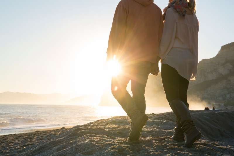 Couple walk hand in hand along beach, sunrise