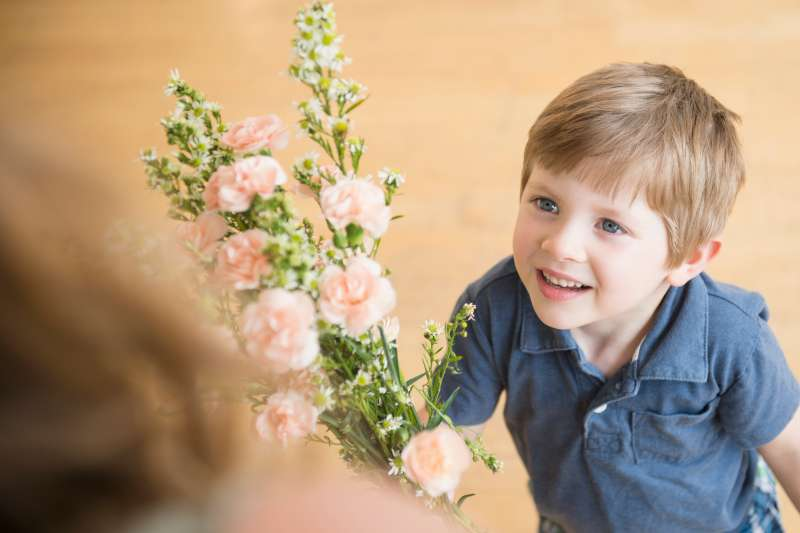 Boy giving bouquet flowers to Mother