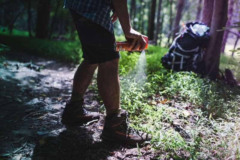 Hiker spraying bug spray with DEET
