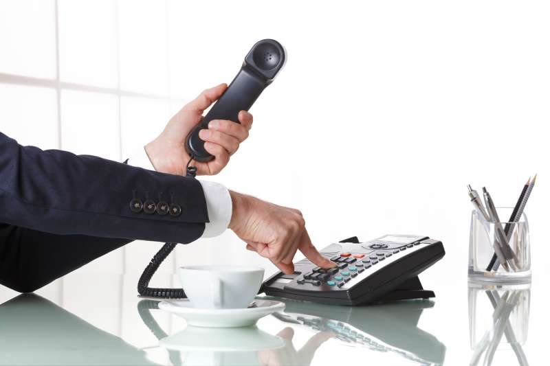 Businessman hands dialing out on a black deskphone