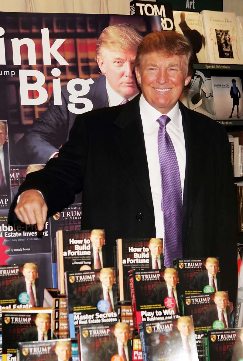 Donald Trump gestures as he poses for a photo during an in-store appearance to sign copies of  How To Build Wealth,  which is a series of nine audio business courses created by Trump University, at a Barnes & Noble store January 10, 2005 in New York City.