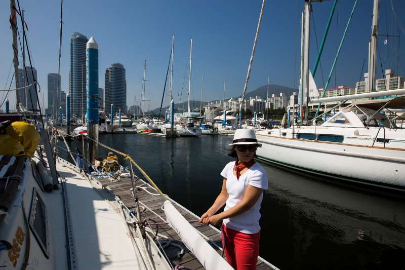 A woman holds a rope as a yacht leaves the Marina in the Haeundae district in Busan, South Korea, on July 31, 2015.