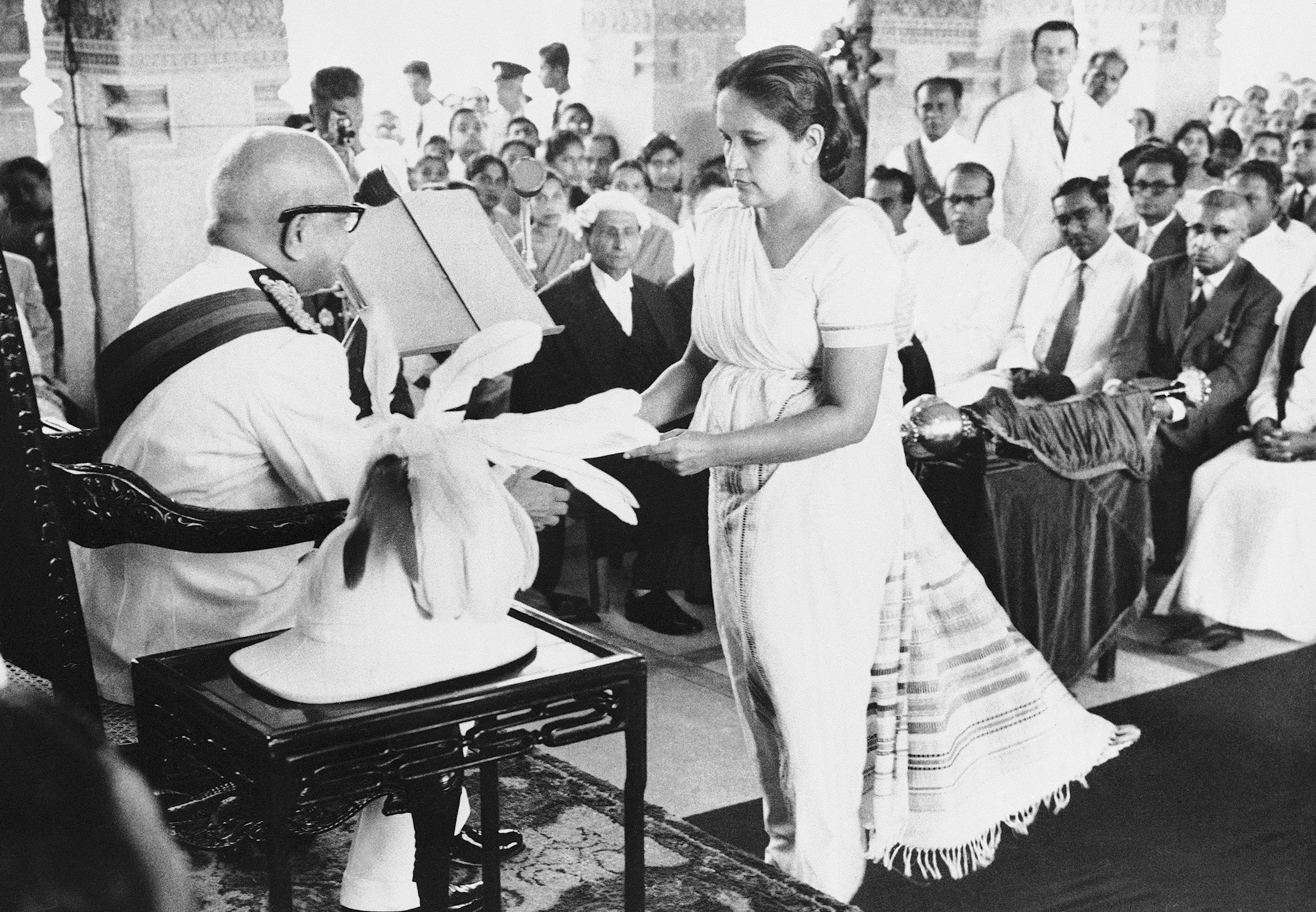The Prime Minister of Ceylon, Mrs. Sirimavo Bandaranaike, hands over a copy of the throne speech to Sir Oliver Goonetilleke, the Governor General of Ceylon, at the ceremonial inauguration of the New Ceylon Parliament in Colombo on August 12, 1960. In the centre background wearing a wig and gown, is Ralph Deraniyagala clerk of the Ceylon House of Representatives. At right are (left to right) T.B. Ilangaratne the minister of trade: Felix Dias Bandaranaike minister of finance: and Dudley Senanayake, leader of the opposition (wearing a dark suit).