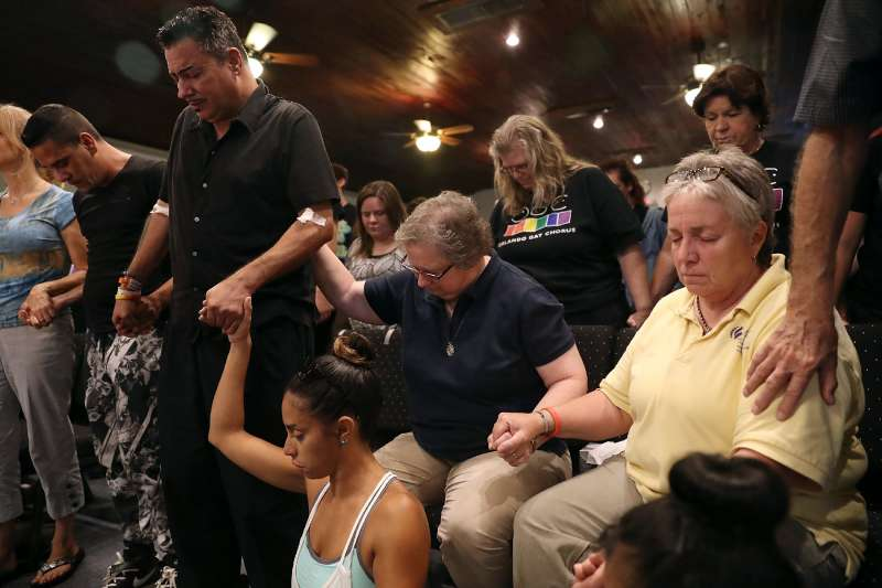 Orlando, second from left, who was injured in the mass shooting at Pulse but did not want his last name used, attends a memorial service at the Joy MCC Church for the victims of the Orlando nightclub shooting.