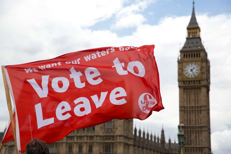 Leave supporters hold flags as they stand on Westminster Bridge during an EU referendum campaign stunt in which a flotilla of boats supporting  Leave  sailed up the River Thames outside the Houses of Parliament in London, Wednesday, June 15, 2016. A flotilla of boats protesting EU fishing polices has sailed up the River Thames to the Houses of Parliament as part of a campaign backing Britain's exit from the European Union. The flotilla was greeted by boats carrying  remain  supporters.