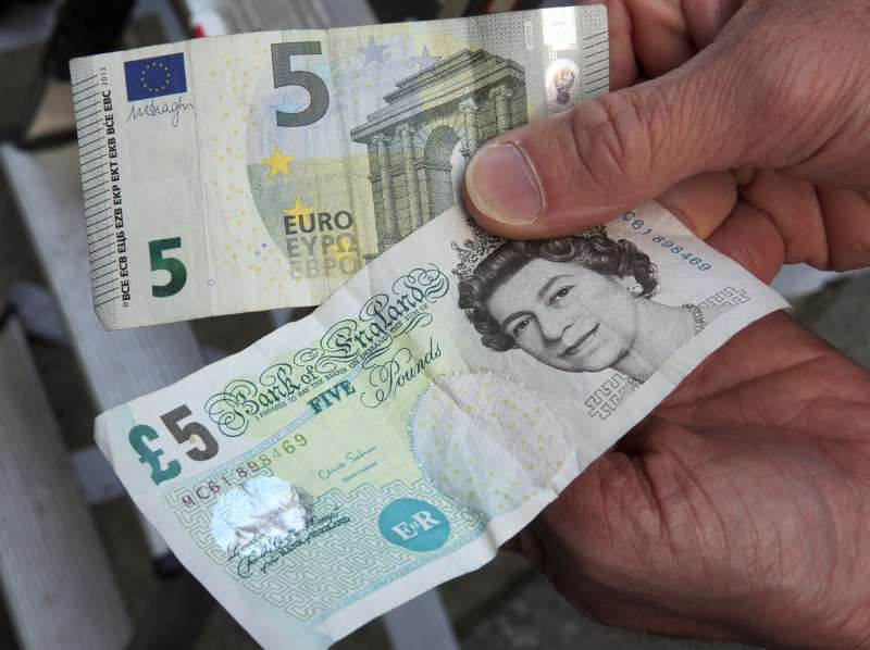 A 5-pound (bottom) and a 5-euro bill are held up in London, Britain, 24 June 2016. In a referendum on 23 June, Britons have voted by a narrow margin to leave the European Union (EU).