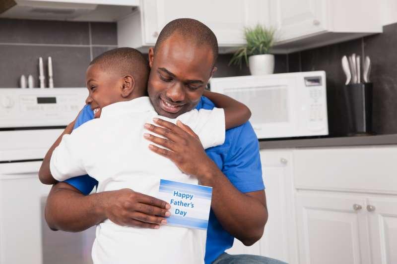 USA, Illinois, Metamora, Man embracing son (6-7), holding 'HappyFather's Day' card