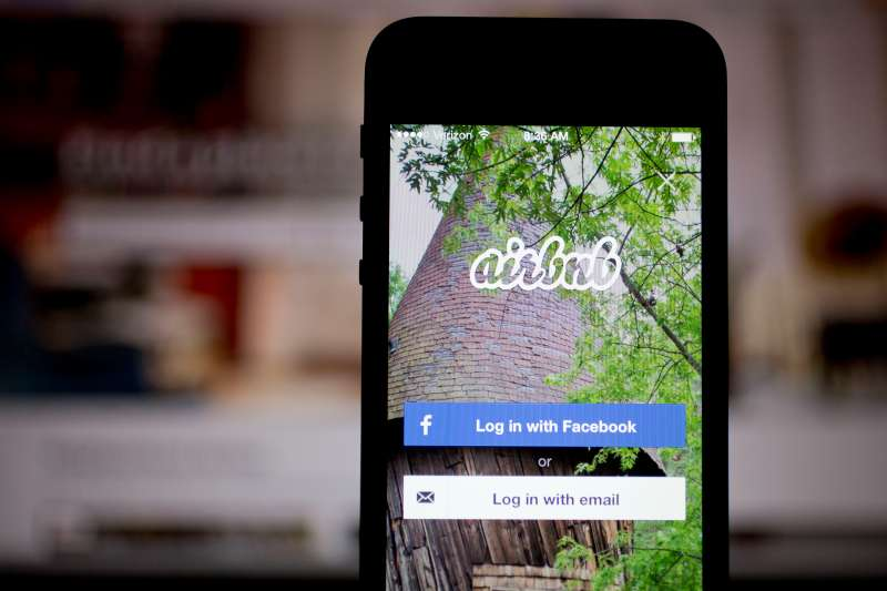 The Airbnb application and website are displayed on an iPhone and iPad.