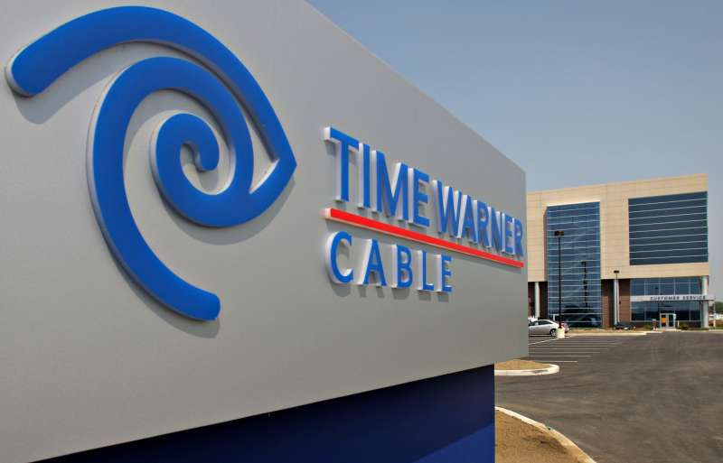 A Time Warner Cable logo appears on a sign outside the compa
