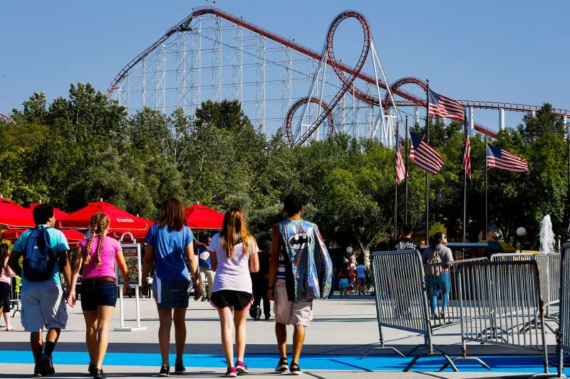 Visitors walk towards a roller coaster at Six Flags Magic Mountain in Valencia, California, on April 20, 2015.