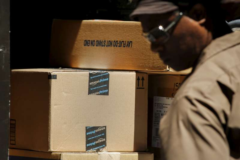 A UPS worker organizes Amazon boxes to be delivered in New York July 24, 2015.
