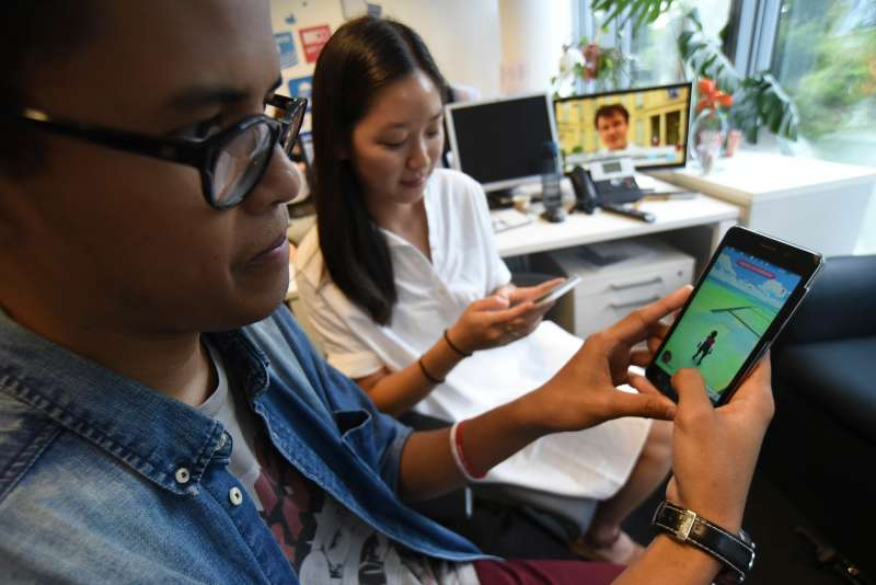 Youths play with the Pokemon Go app on their smartphone. Millions of users have already downloaded the game, which requires users to catch on-screen pokemon characters using their real-world location. Shares in the gaming company Nintendo jumped by nearly a quarter following the app success.