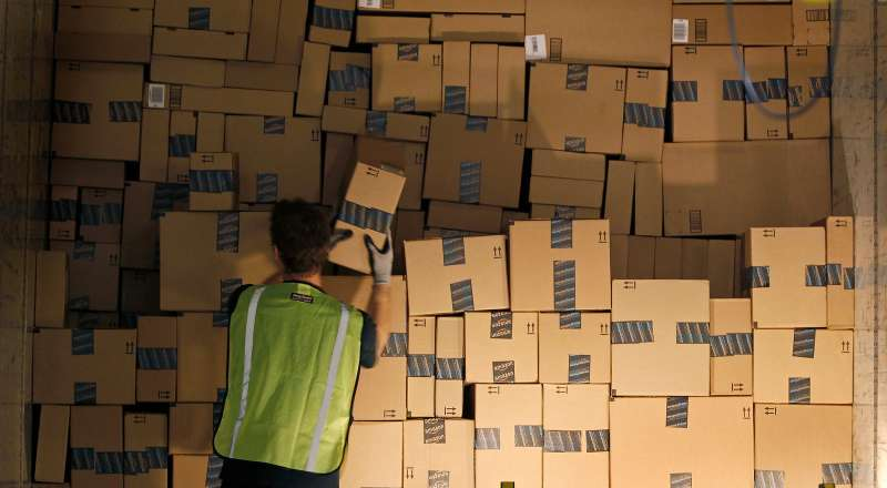 A worker stacks a shipping trailer with boxed items for delivery at Amazon's distribution center in Phoenix, Arizona November 22, 2013.