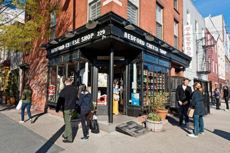 A cheese shop is a gathering point for people on Bedford Avenue in the Williamsburg neighborhood in Brooklyn, New York City, 2013.