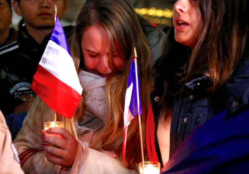 Members of the Australian French community cry as they sing the French national anthem during a vigil in central Sydney, Australia, on July 15, 2016, to remember the victims of the Bastille Day truck attack in Nice.