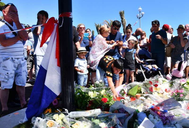 People visit the scene and lay tributes to the victims of a terror attack on the Promenade des Anglais on July 15, 2016 in Nice, France. A French-Tunisian attacker killed 84 people as he drove a lorry through crowds, gathered to watch a firework display during Bastille Day celebrations.