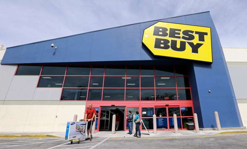 In this Feb. 9, 2016 photo, a shopper carts his purchased LED TV at a Best Buy in Miami.