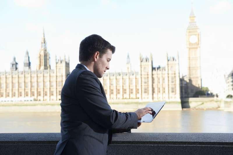 business man using digital tablet near westminster