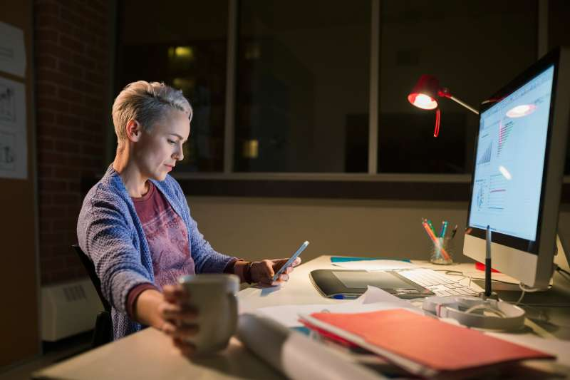 Designer with cell phone working late at desk