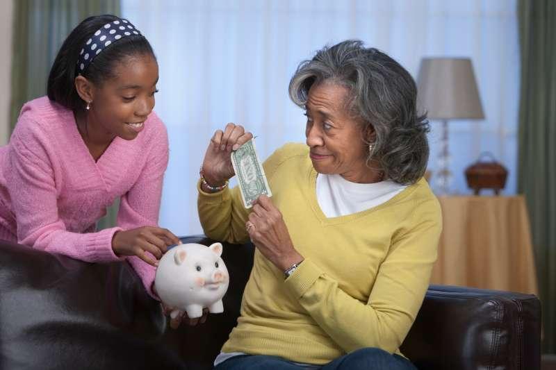 African woman giving granddaughter dollar bill for piggy bank