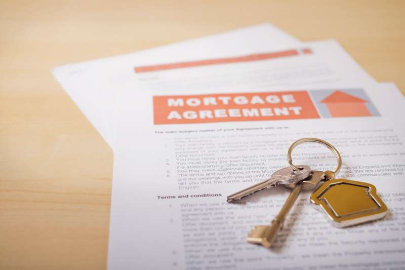 House keys and mortgage loan agreement on desk, close-up (differential focus)