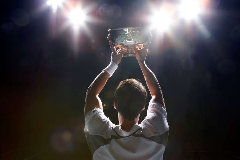 man holding trophy from rear, backlit
