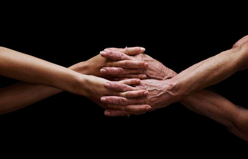 old and young hands intertwined