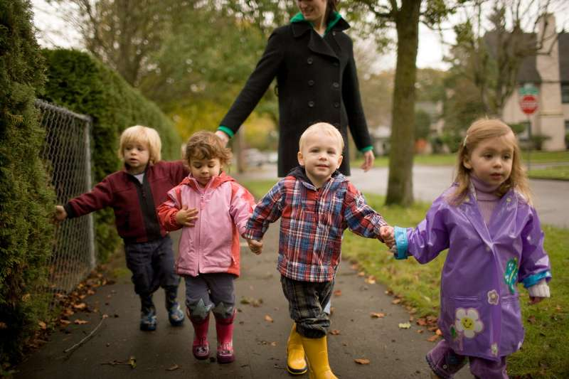 babysitter walking with four kids in daisy chain