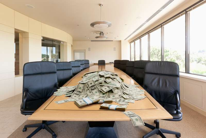 piles of money on conference table