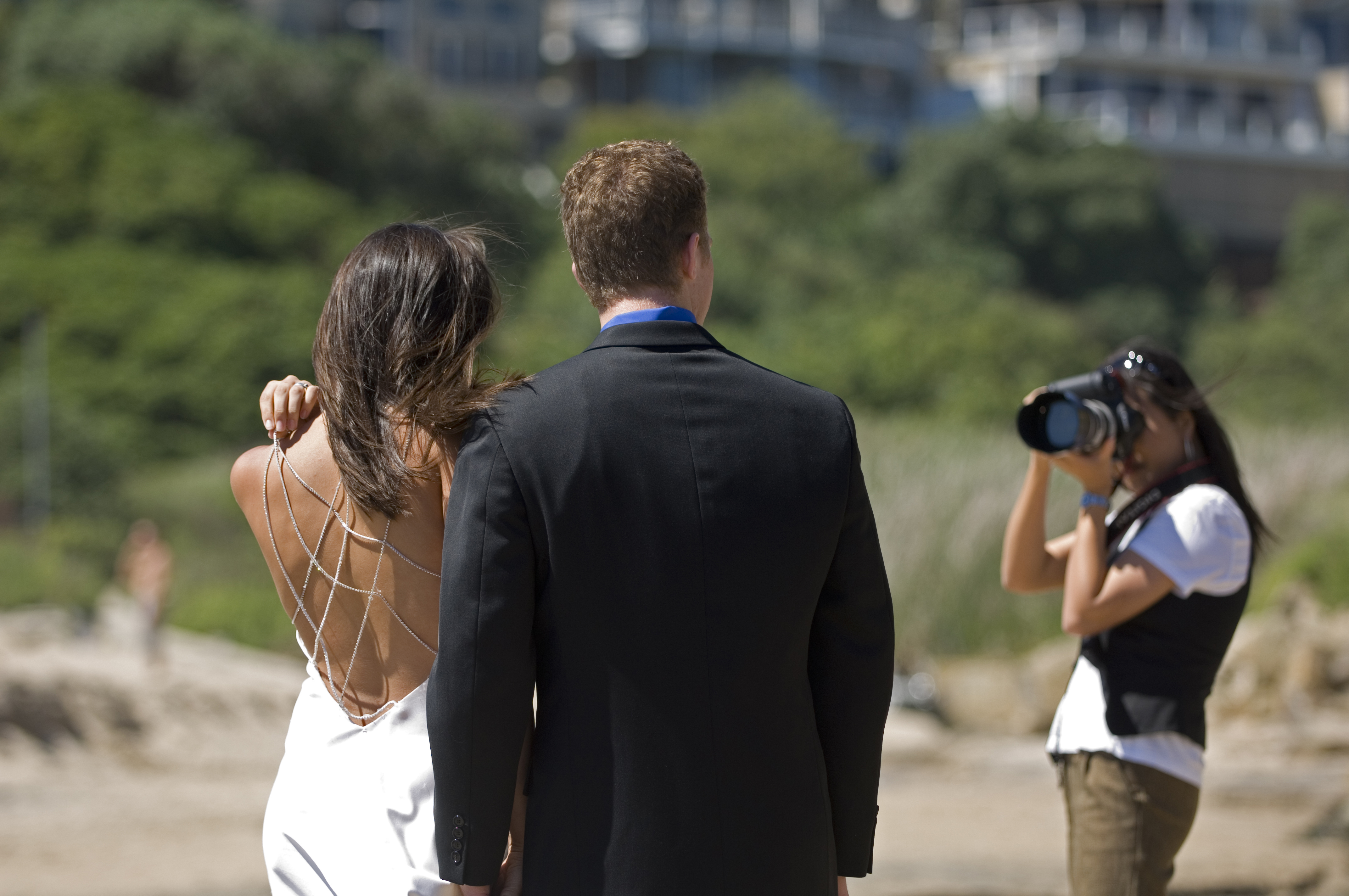 Female photographer shooting couple at wedding ceremony on the beach