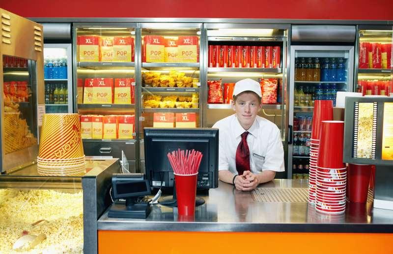 Teenage boy (14-16) serving at popcorn counter, smilng, portrait