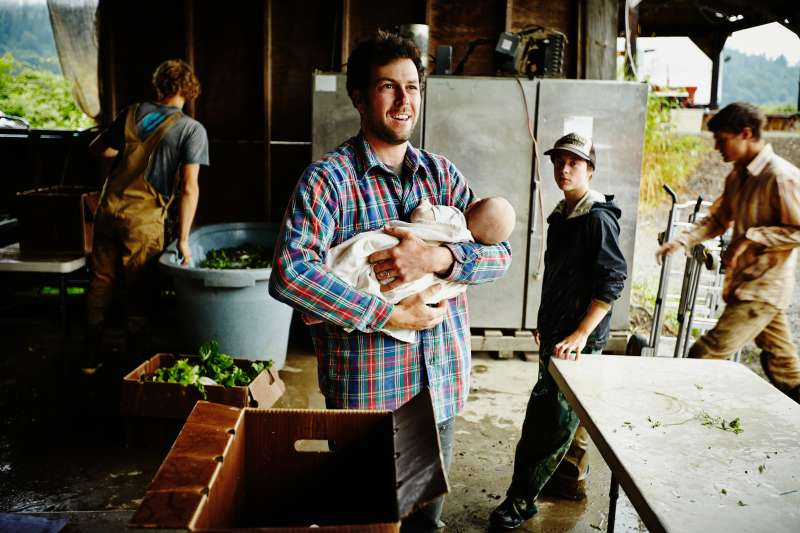 Farmer holding infant standing in work shed