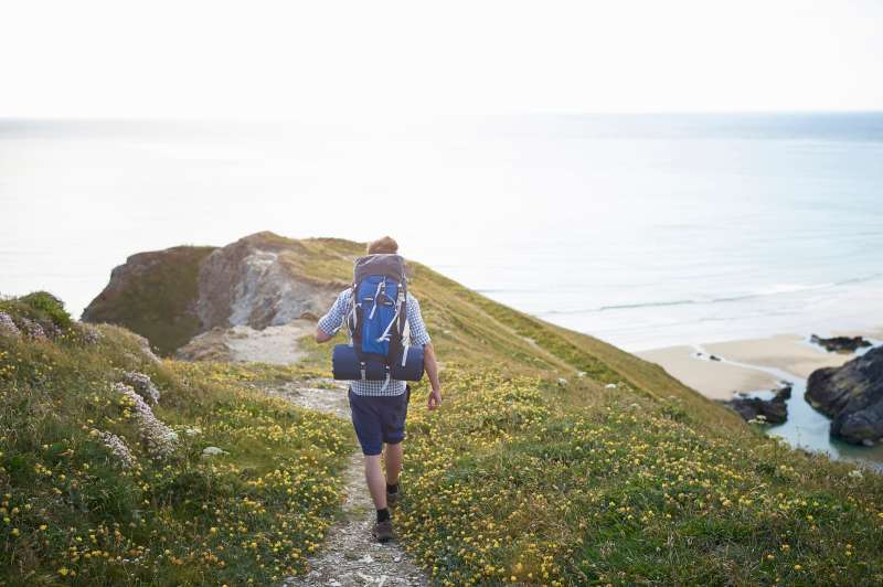 Hiker walking along coastal path