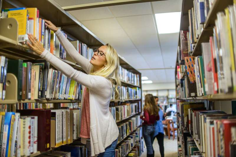 Young female librarian arranging books on library shelves