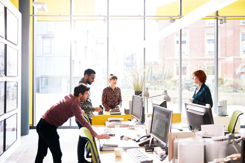 Coworkers talking over ideas in open plan office