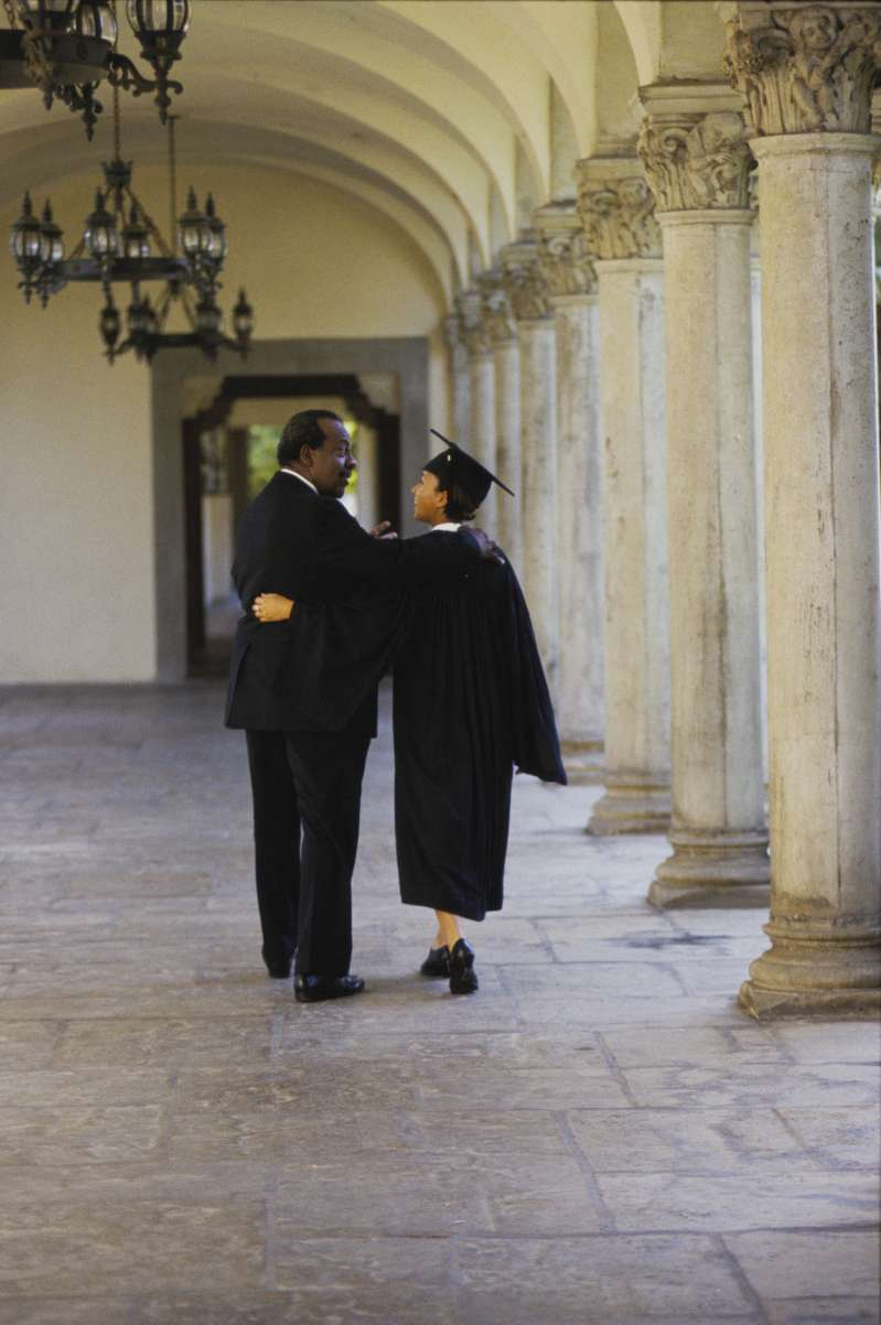 Female graduate with father in hallway