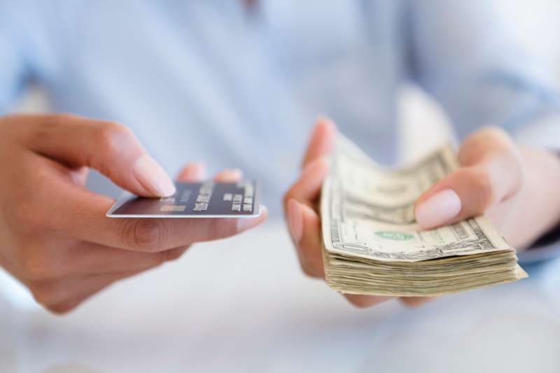person holding credit card and stack of cash