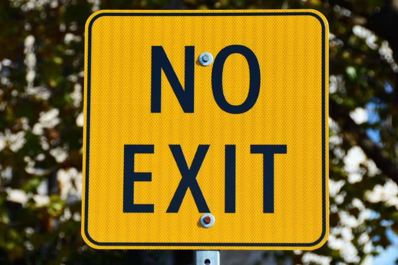 A rectangular gold sign with black lettering says no exit,no way out.