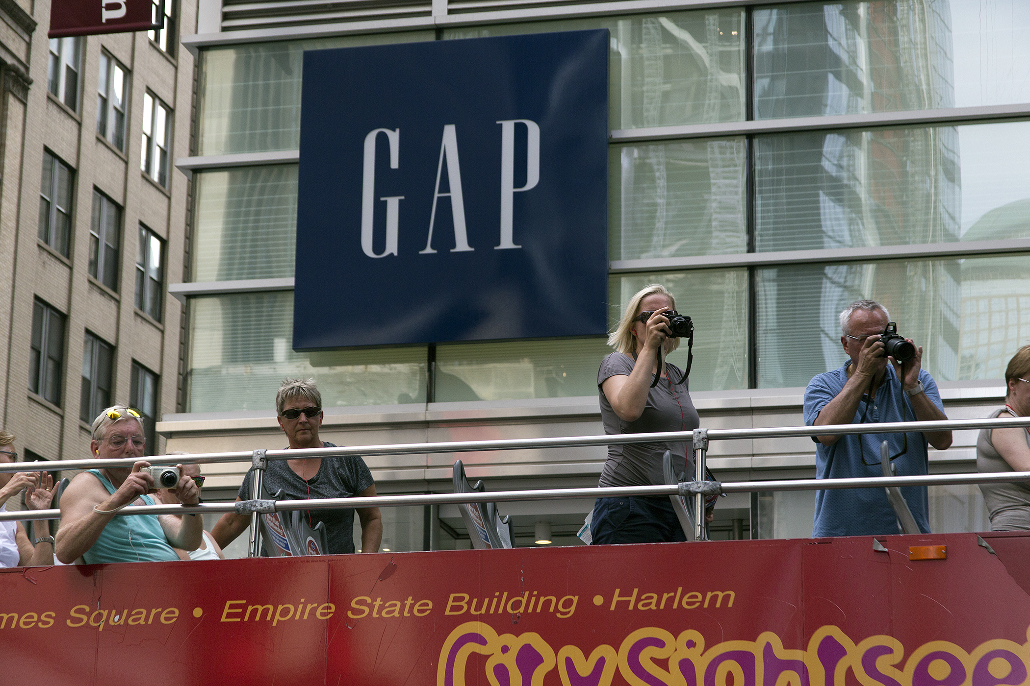 Tourists on a New York City sightseeing bus take photos in front of the GAP store, 400 Fulton Street.