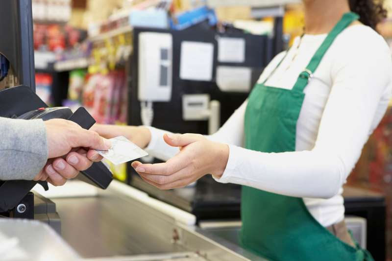 man handing card to cashier in store
