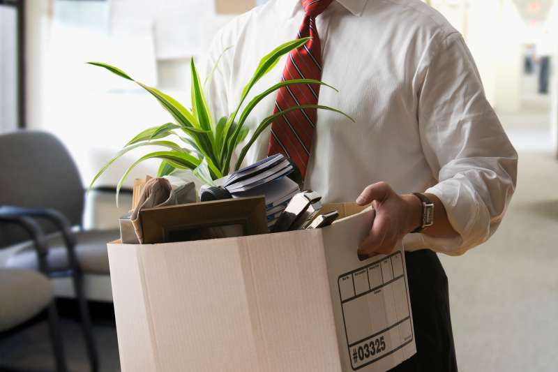 man carrying box of personal items out of office