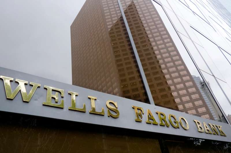 In this May 5, 2015, file photo, a downtown building is reflected in the windows of a Wells Fargo Bank in Los Angeles.