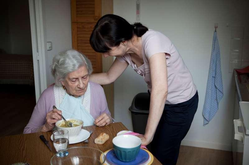 woman helping elderly woman eat