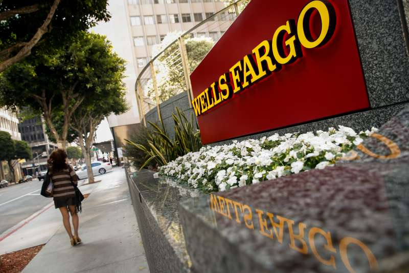 A woman walks past a Wells Fargo & Co. bank branch in Los Angeles, California, U.S., on Tuesday, July 7, 2015.