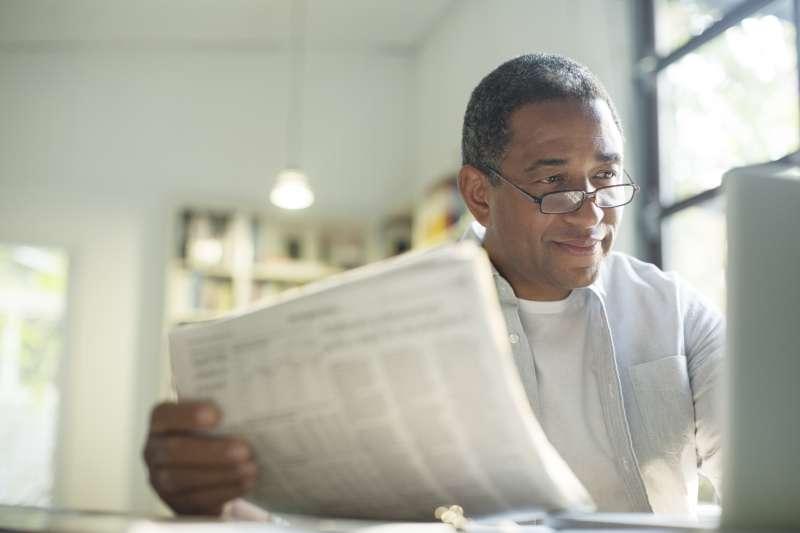 Senior man with newspaper using laptop