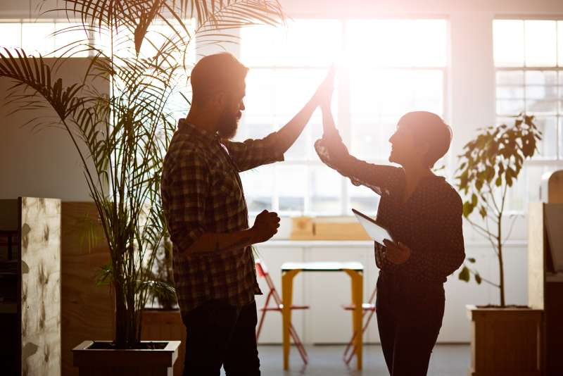 Creative coworkers doing high five at the office