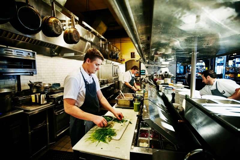 Line cook preparing cilantro in restaurant kitchen