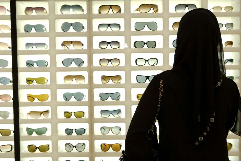 A young Emirati woman shopping for sunglasses.