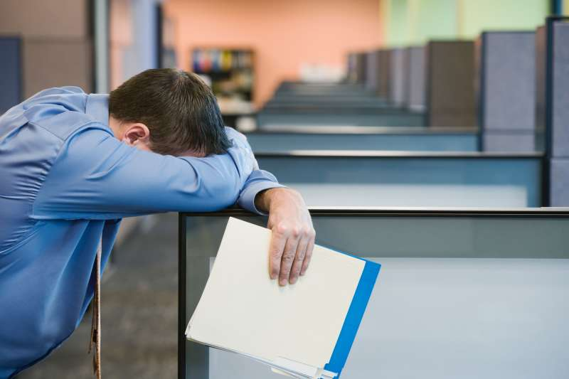 Businessman leaning head on cubicle wall