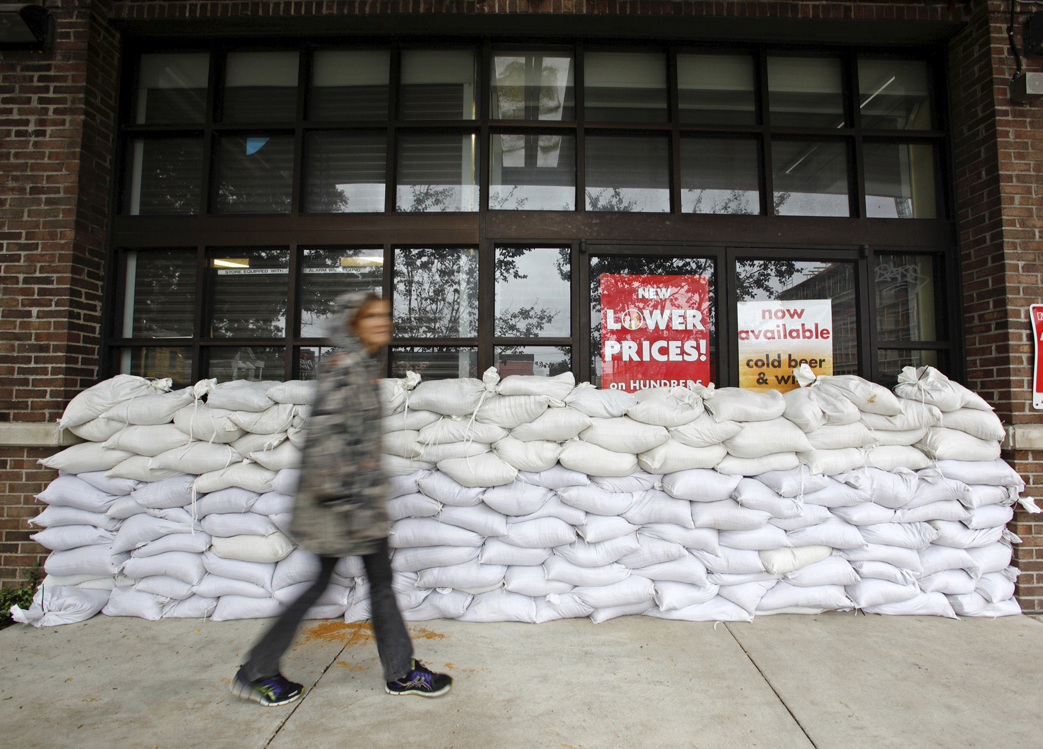 A resident walks past a wall of sandbags protecting a store in one of the city's low-lying areas before the arrival of Hurricane Matthew, in Charleston, South Carolina,  October 7, 2016.